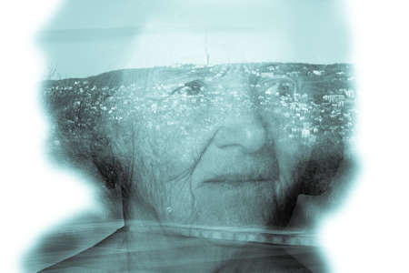 grayness: Landscape shines through the portrait of an elderly woman. Toned.
