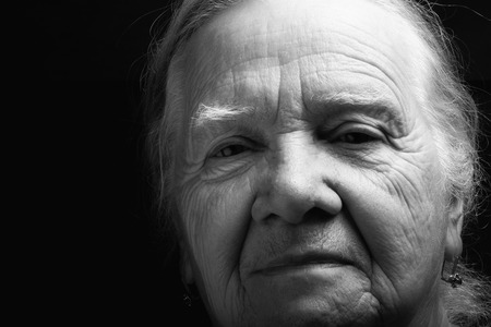 grayness: Portrait of elderly woman. Serious. Toned.