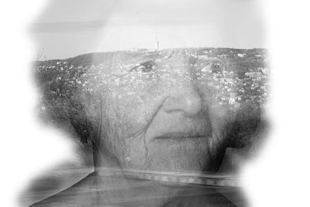 grayness: Landscape shines through the portrait of an elderly woman.