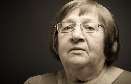 grayness: Portrait of elderly woman. Attention. Toned.