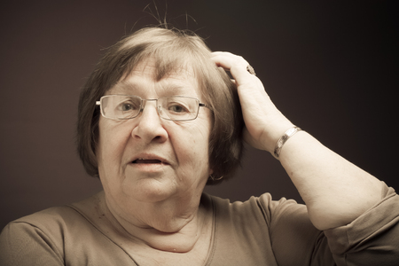 Portrait of elderly woman. Question. Toned. Stock Photo