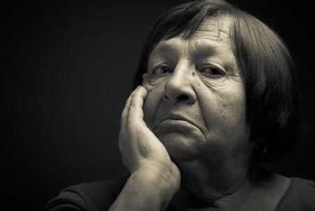 grayness: Portrait of elderly woman. Perplexity. Toned.