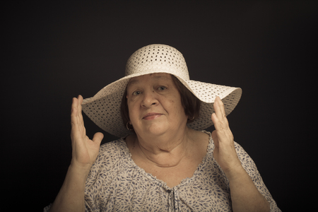 grayness: Portrait of elderly woman with a hat. Question. Toned.