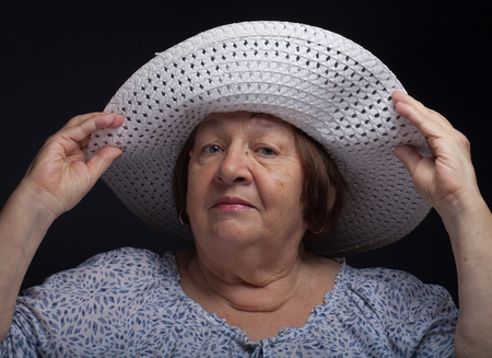 grayness: Portrait of elderly woman with a hat. Toned. Stock Photo