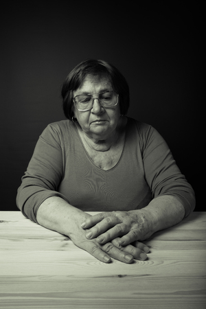 Portrait of elderly woman at a wooden table. Dreaminess. Toned.