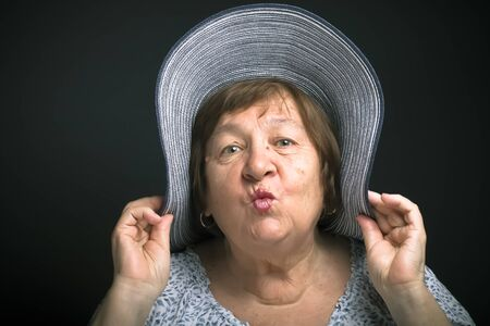 Portrait of elderly woman with a hat. Kiss. Toned. Stock Photo