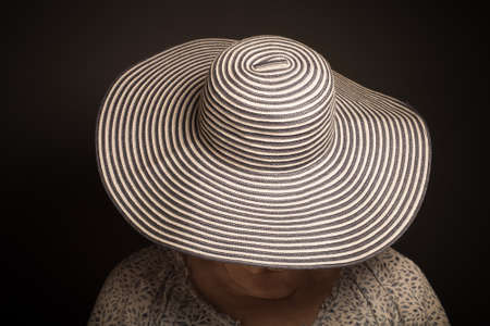 grayness: Portrait of elderly woman. Face covered hat. Toned. Stock Photo