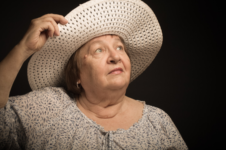 Portrait of elderly woman with a hat. Dream. Toned. Stock Photo