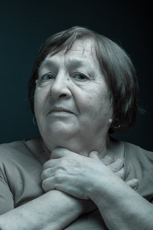 grayness: Portrait of elderly woman. Question. Toned. Stock Photo