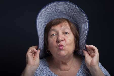 Portrait of elderly woman with a hat. Kiss.