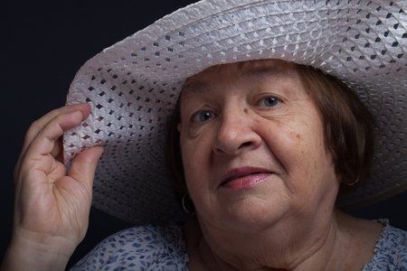 grayness: Portrait of elderly woman with a hat. Question.
