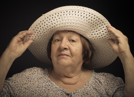 Portrait of elderly woman with a hat. Question. Toned.
