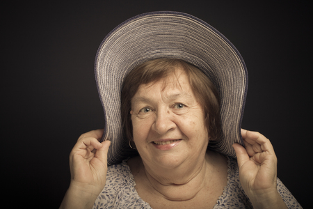 grayness: Portrait of elderly woman with a hat. Smile. Toned.