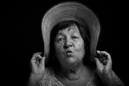 grayness: Portrait of elderly woman with a hat. Kiss. Toned. Stock Photo