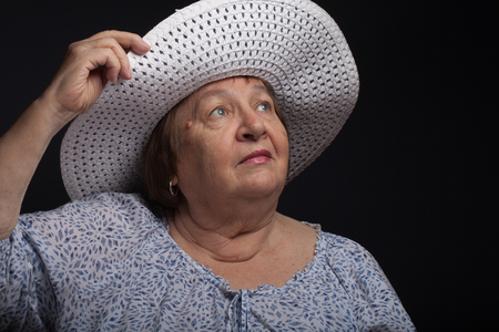 grayness: Portrait of elderly woman with a hat. Dream. Stock Photo