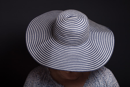 grayness: Portrait of elderly woman. Face covered hat.