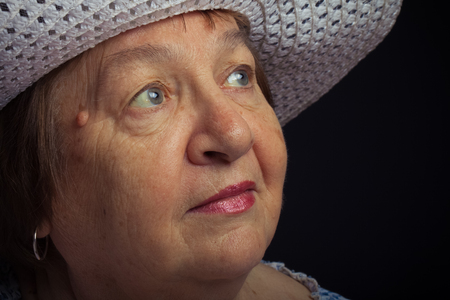 grayness: Portrait of elderly woman with a hat. Dream. Toned. Stock Photo
