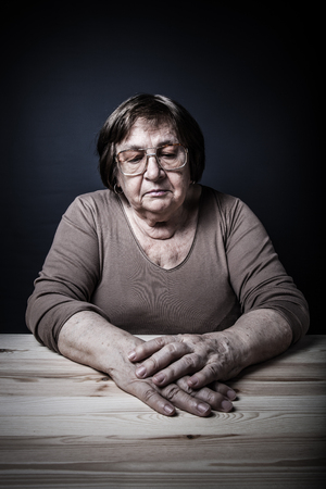 grayness: Portrait of elderly woman at a wooden table. Dreaminess. Toned.