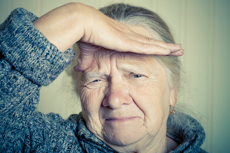 grayness: Portrait of an elderly woman with hand near face on a light background. Toned.