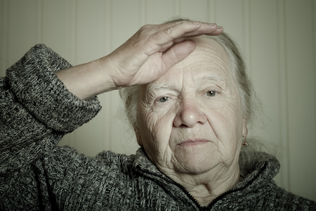 Portrait of an elderly woman with hand near face on a light background. Toned.