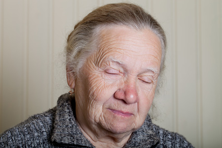 grayness: Portrait of an elderly woman on a light background.