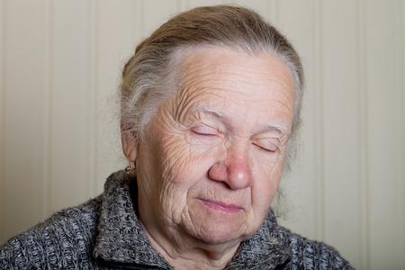 grayness: Portrait of an elderly woman on a light background.