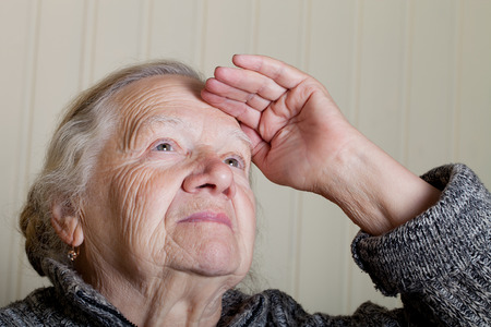 grayness: Portrait of an elderly woman with hand near face on a light background. Stock Photo