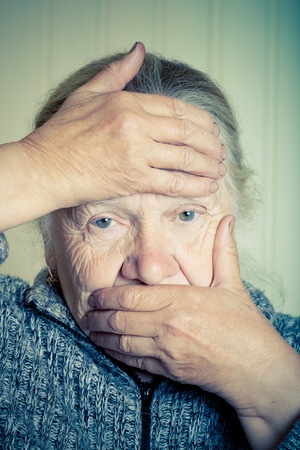 grayness: Portrait of an elderly woman with hands near face on a light background. Toned. Stock Photo