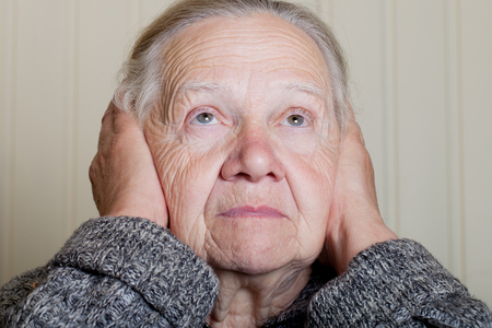 grayness: Portrait of an elderly woman with hands near face on a light background.