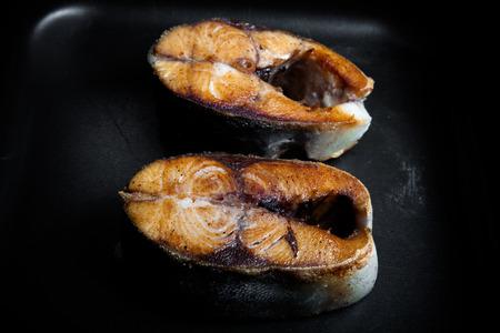 Fried tuna fish on a black pan. Toned.