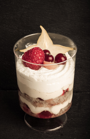 pumpernickel: Small snacks trifle with fruits and cream in plastic glass on a black slate plate. Toned.
