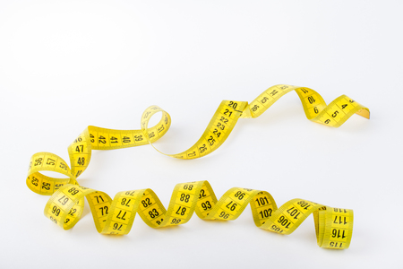 Yellow color centimeter with black figures for measurement of length and width on a white background. Selective focus.