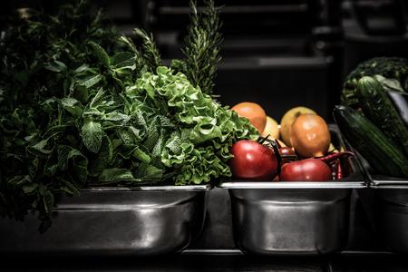 Verse greens in metaalkom op professionele keuken. Selectieve aandacht. Ondiepe scherptediepte. Afgezwakt.