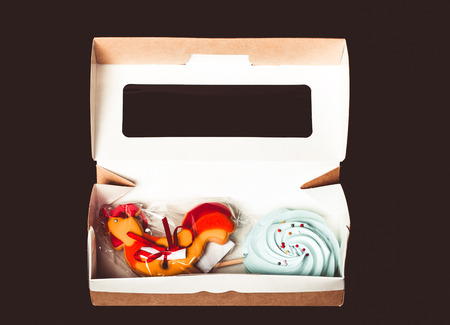 kiss biscuits: Blue round merengue on a stick and new year gingerbread with glaze in a paper box with plastic window. Festive set. Toned. Stock Photo