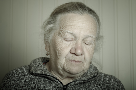grayness: Portrait of an elderly woman with closed eyes. Toned.