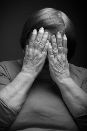grayness: Portrait of elderly woman. Eyes closed by hands. Toned. Stock Photo