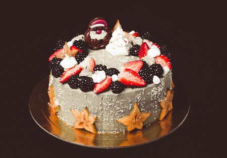 Homemade cake with new year decor on a black background. Toned. Stock Photo