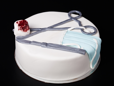 pinzas: Homemade cake with medical decor on a black background.