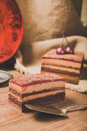 Homemade cherry cake with chocolate decor on a rustic style background. Selective focus. Toned.