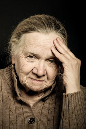wistfulness: Portrait of elderly woman on dark background. Wistfulness. Toned.
