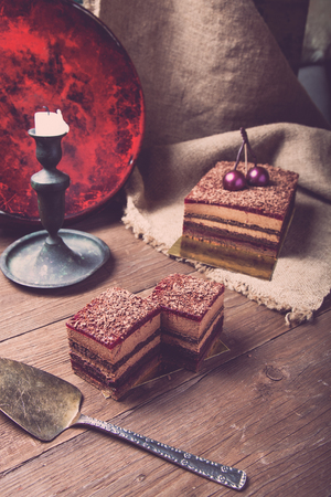 bordo: Homemade cherry cake with chocolate decor on a rustic style background. Selective focus. Toned.