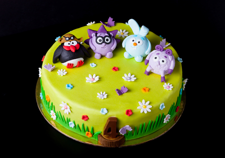 Homemade cake with mastic for childrens birthday on a black background. Animation theme - smeshariki. Reklamní fotografie