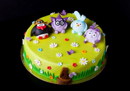 Zelfgemaakte cake met mastiek voor de verjaardag van kinderen op een zwarte achtergrond. Animatiethema - smeshariki.
