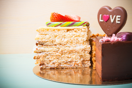 Pieces of homemade cakes with different Valentines day decor on a light background. Toned.