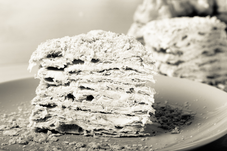 topper: Homemade puff cake with brewed creamy cakes as decor on a light background. Shallow depth of field. Selective focus. Toned. Stock Photo