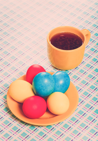 gingerbread: Easter eggs and cup of tea on light background. Toned.