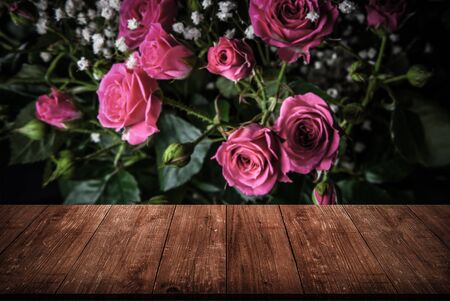 View from wooden table on wonderful bouquet of bush roses and gypsophila on a dark background. Selective focus. Shallow depth of field. Toned.