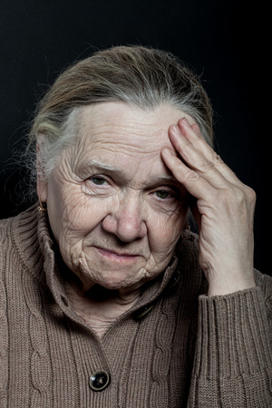 wistfulness: Portrait of elderly woman on dark background. Wistfulness. Stock Photo