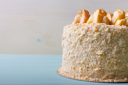 Homemade puff cake with brewed creamy cakes as decor on a light background.