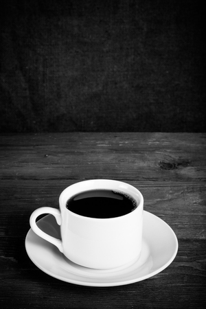 White cup of tea on old wooden table against the background of burlap. Selective focus. Shallow depth of field. Toned.